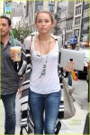 Miley Cyrus, carrying an iced coffee and Apple iPad, shows off her lacy, animal print bra while wearing a sheer white top